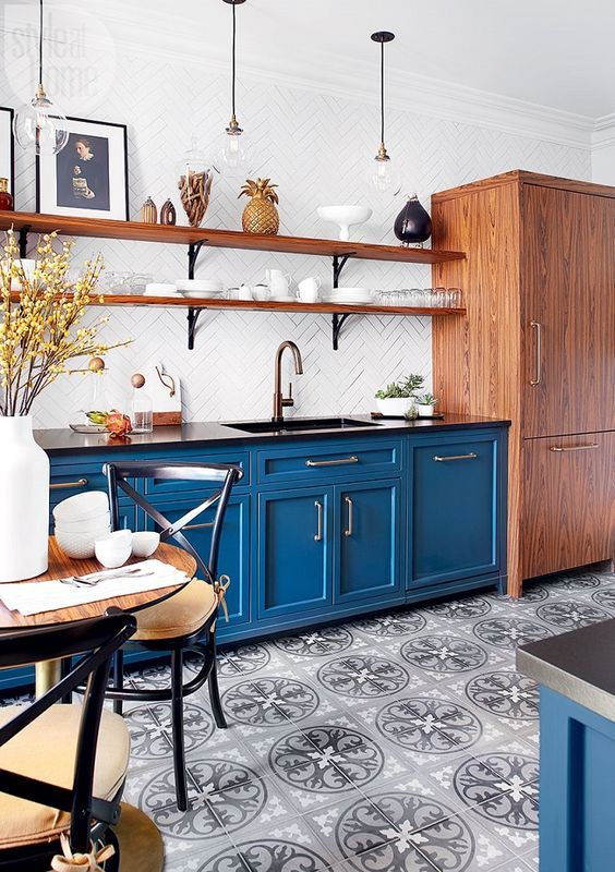a bold blue kitchen with a printed tile floor, wooden shelves and a storage unit, black chairs with cushions is welcoming