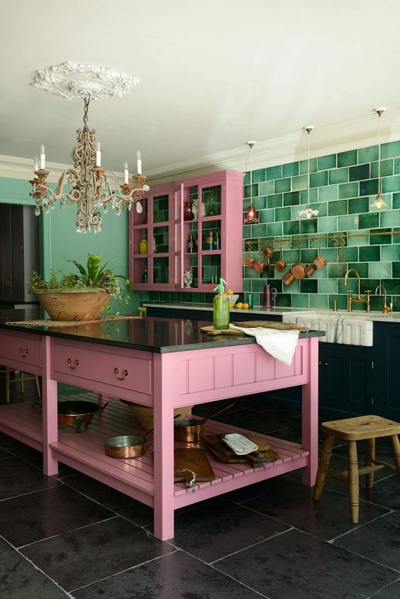 a bold kitchen with black lower cabinets, upper pink ones, a pink kitchen island, a bold green tile backsplash and a chic chandelier