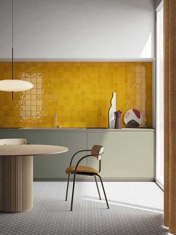 une cuisine moderne audacieuse avec des armoires gris olive, un dosseret en carreaux jaunes et une table et des chaises raffinées est wow