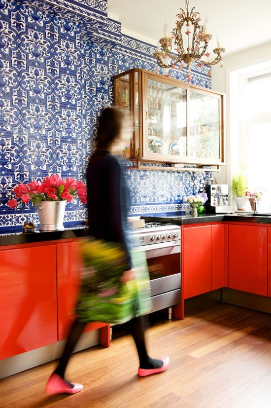 a bold red kitchen with a blue patterned tile wall, a glass cabinet and a refined and chic chandelier over the space