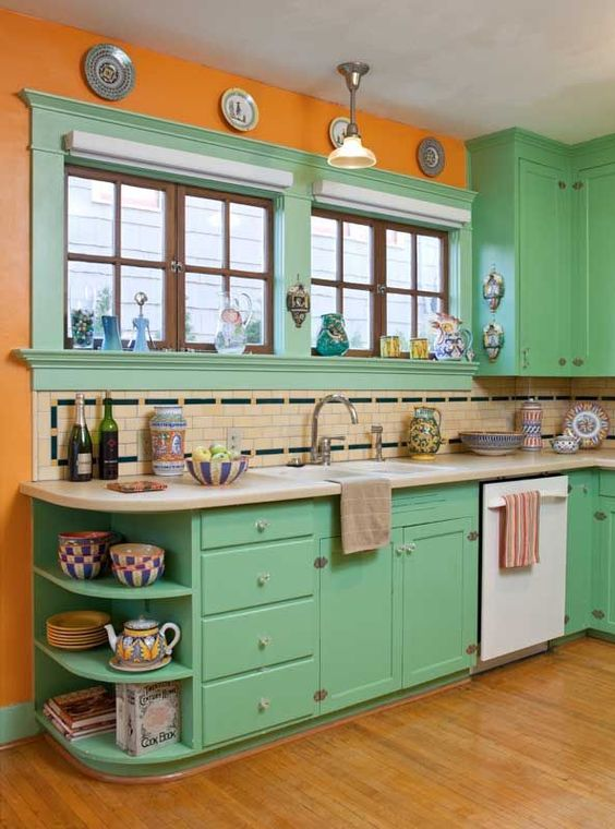 a bold retro ktichen in green, with orange walls, a neutral and black tile backsplash and decorative plates on the wall
