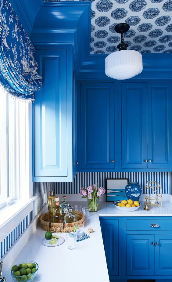 a bright blue kitchen with a striped backsplash and a bold wallpaper ceiling looks siper bright and very elegant, seaside inspired