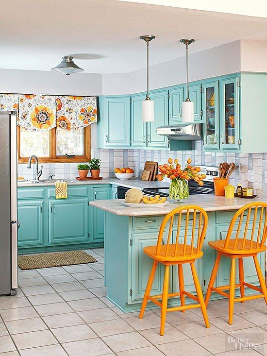a bright blue kitchen with a tiled backsplash, orange chair, floral shades and retro lamps is a very cool idea