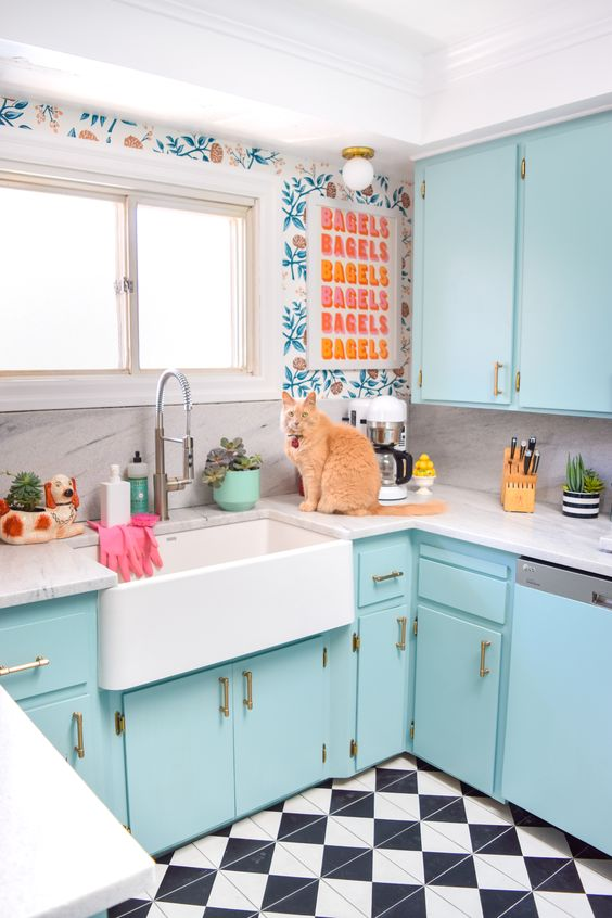 a bright blue kitchen with printed wallpaper, a colorful artwork and a tiled floor is fun and welcoming
