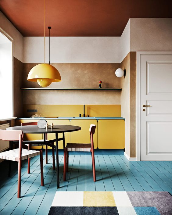 a bright modern kitchen with yellow cabinets and a pendant lamp, a blue floor and blue countertops plus a geometric rug