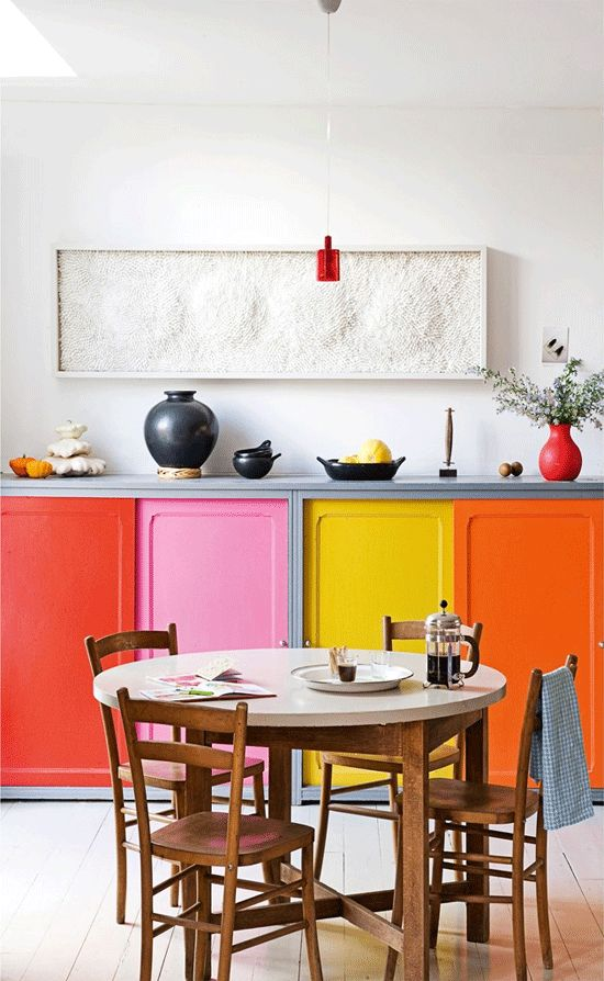 a colorful kitchen with bold doors, and a round table, wooden chairs and a pretty textural artwork and red touches