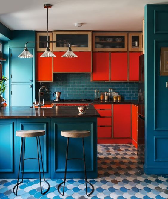 a colorful kitchen with bright red cabinets, navy cabinets, walls and a backsplasj plus a retro pendant lamp and a scallop tile floor