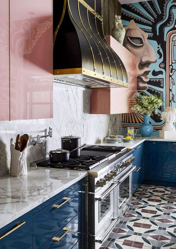 a colorful kitchen with navy lower cabinets, pink upper ones, a marble backsplash and a vintage hood to make a statement
