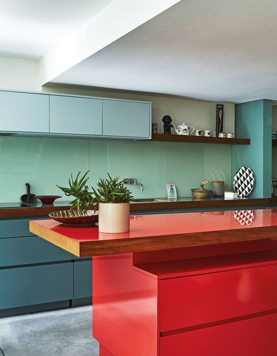 a minimalist kitchen with blue and muted blue cabinets, a mint green backsplash, a bold red kitchen island and wooden countertops
