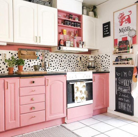 a playful kitchen with pink and white cabinetry, a Dolmatin backsplash and brass handles and fixtures is bold and cool