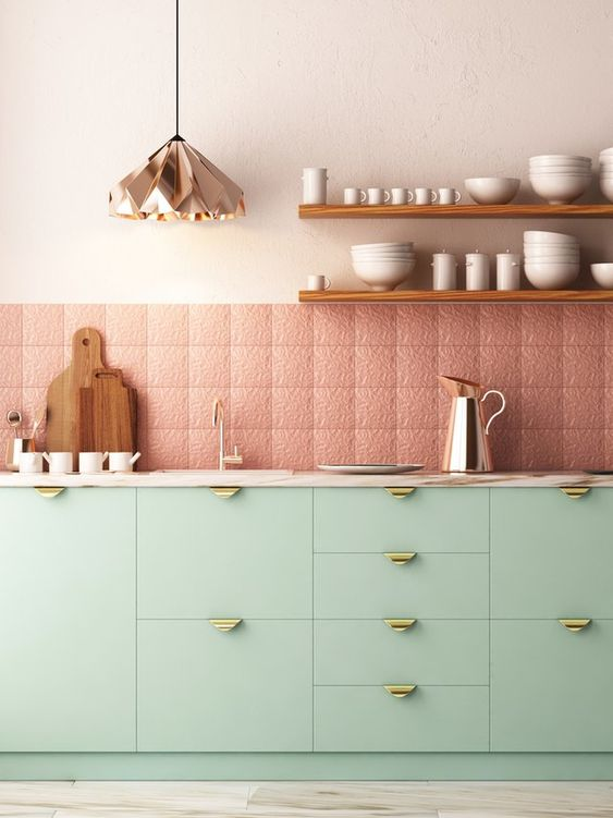 a pretty contemporary kitchen with mint cabinetry and gold handles, patterned and textural pink tiles, a copper geometric pendant lamp