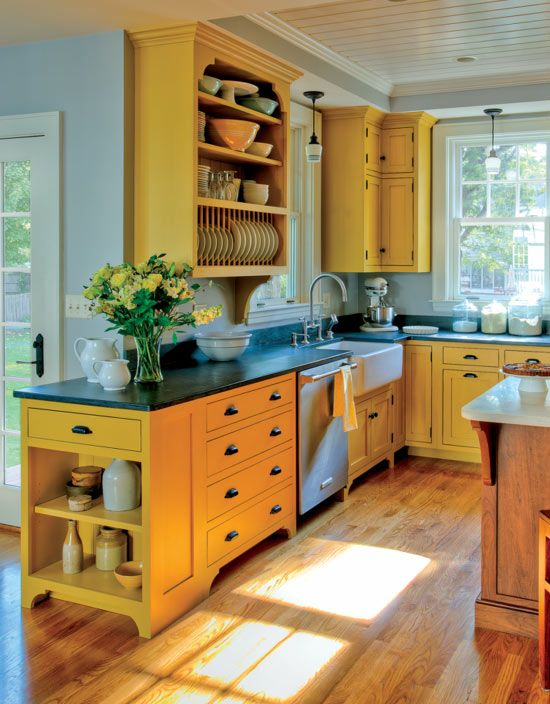 a sunny yellow kitchen with black coutnertops, a wooden kitchen island looks very inspiring, bold and cool