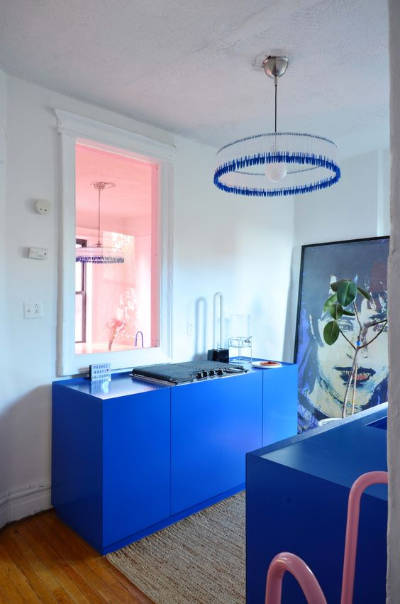 a super bold blue, yet small kitchen with not many cabinets, a statement artwork and a bright blue chandelier