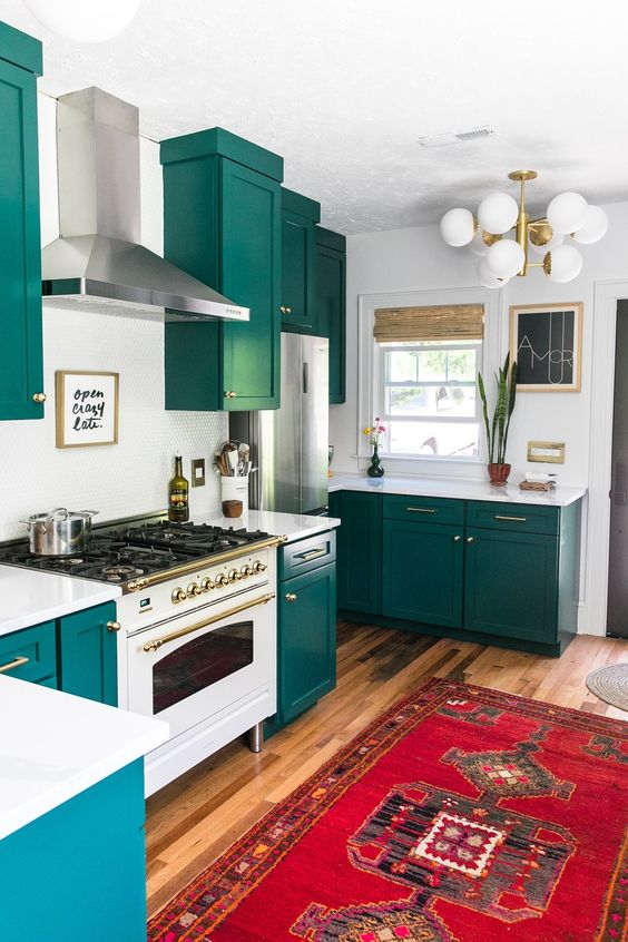 a teal kitchen with white countertops, a backsplash and a bold boho rug plus a retro lamp is a cool idea