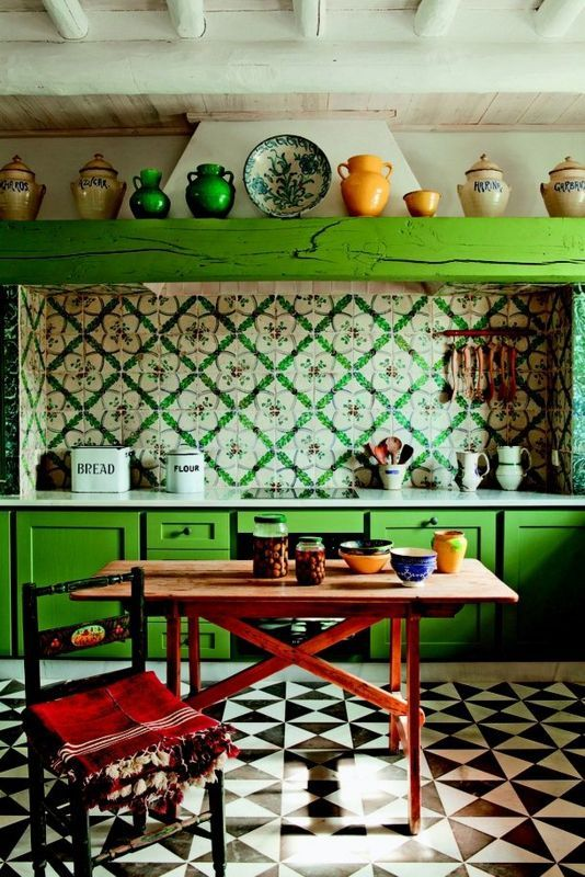 an eclectic kitchen with bold green cabinets, bright printed tiles on the backsplash, a wooden table and a chair plus colorful tableware