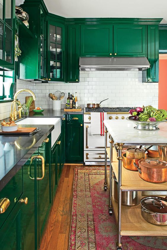 an emerald kitchen with a white subway tile backsplash, elegant gold touches and a bright boho rug