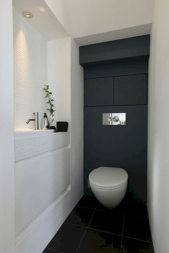 a black and white guest toilet with a built-in sink, some built-in lights and even storage