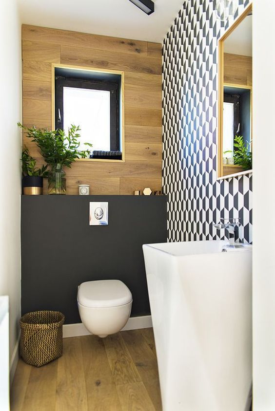 a chic guest toilet with a geometric wall, a plywood one, a blakc accent, a free-standing sink and a fabric basket