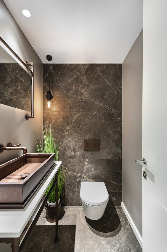 a chic guest toilet with stone tiles, a large metal sink, a fake potted plant and some pipes for an industrial feel