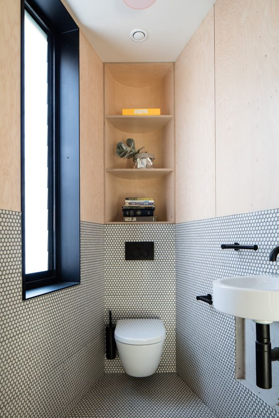 a contemporary guest toilet with a frosted glass window, penny tiles and plywood, with storage shelves and a wall-mounted sink