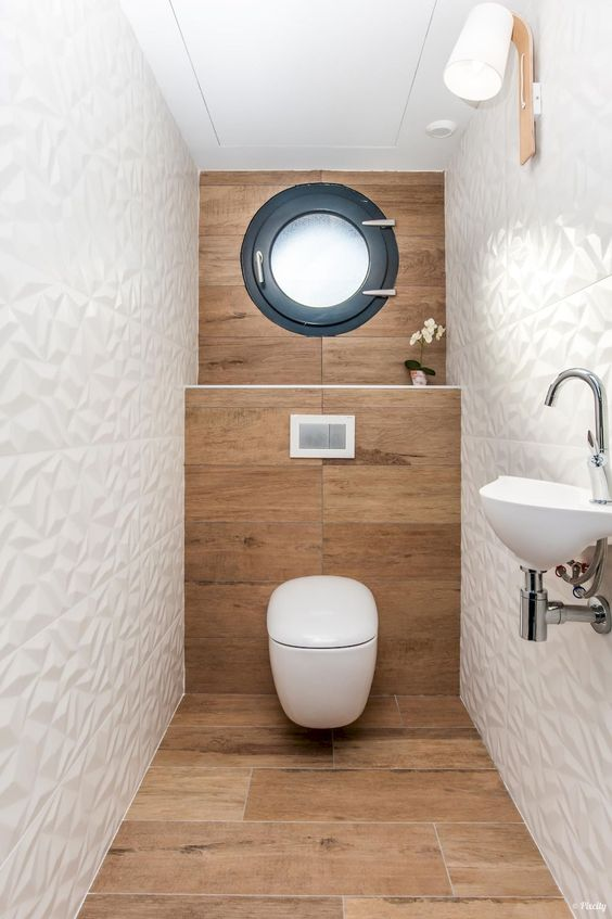 a contemporary guest toilet with wood-inspired tiles, geometric white ones, a window, a wall-mounted sink