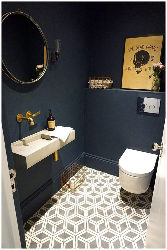 a cool guest toilet with navy walls, a geometric floor, an artwork and brass fixtures for a chic look