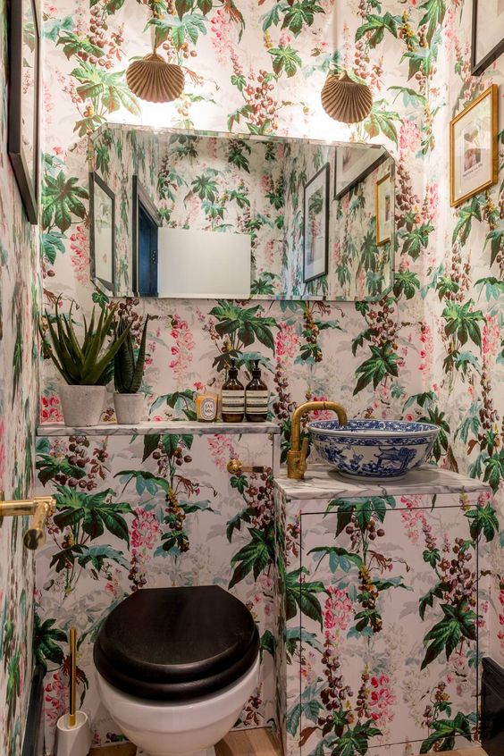 a crazy guest toilet done with bright floral wallpaper, a vanity covered with it, a mirror, some lamps and gold touches