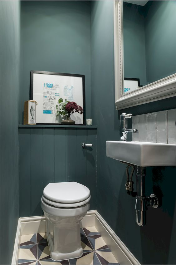 a guest toilet done with teal walls, a large mirror in a frame, some artworks and a wall-mounted sink