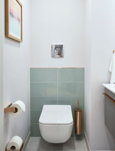 a laconic guest toilet with aqua tiles, copper touches and a floating vanity with a sink