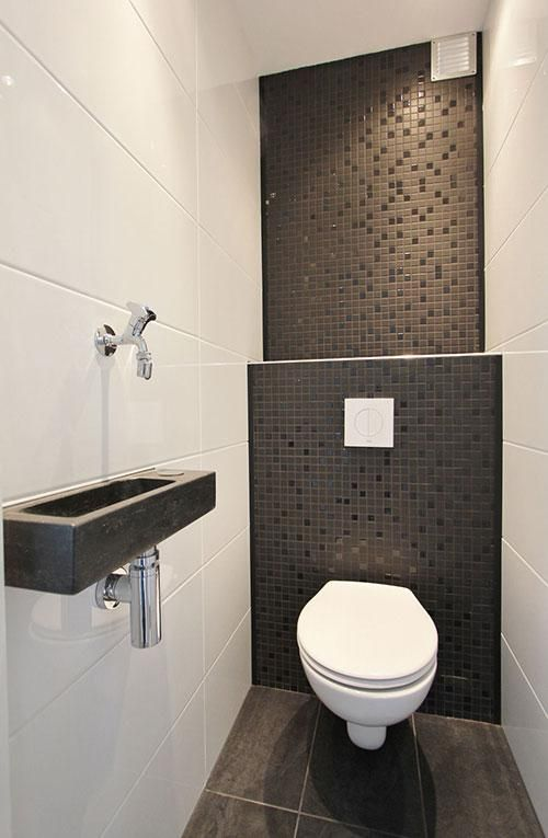 a monochromatic guest toilet with black and white tiles of different scales and a wall-mounted stone sink