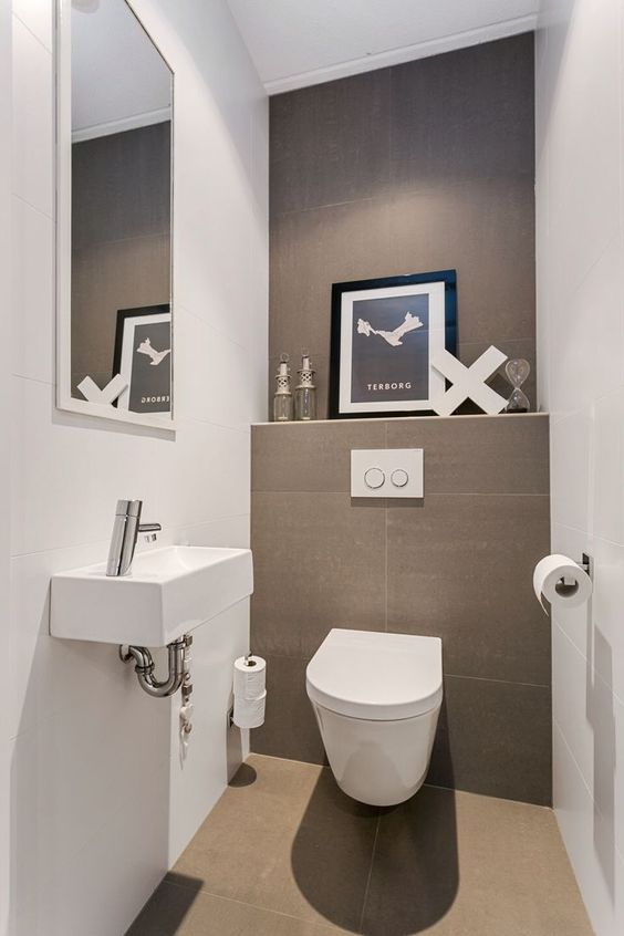 a neutral guest toilet done in taupe and white, an artwork, a wall-mounted sink and a large mirror