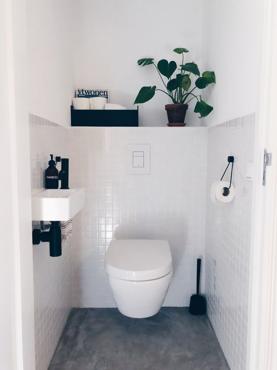 a neutral guest toilet with black touches for some drama, a wall-mounted sink and a box with storage