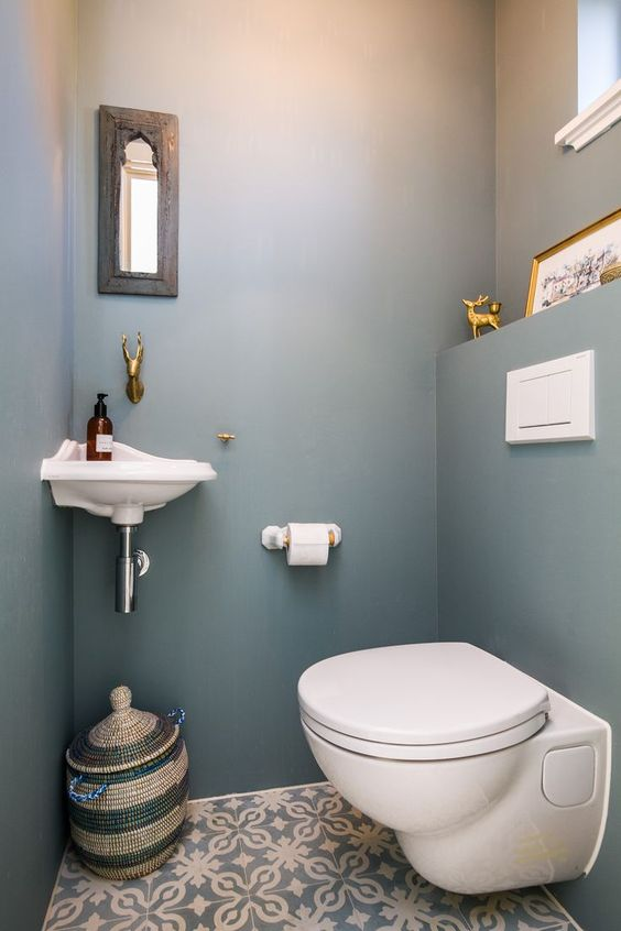 a small and simple guest toilet with a tiny wall-mounted sink, a small mirror, a basket for storage and a toilet