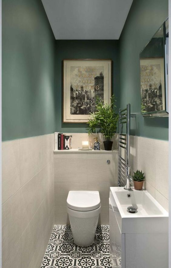 a small and stylish guest toilet with green and white tile walls, a sink with a vanity for storage and some artworks