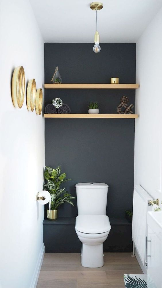 a small black and white guest toilet with a shelf, some gilded frame mirrors and a potted plant
