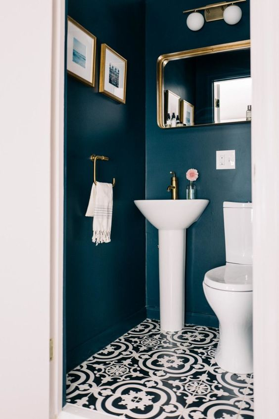 a stylish guest toilet with navy walls, brass fixtures, a mirror and artworks plus a wall lamp