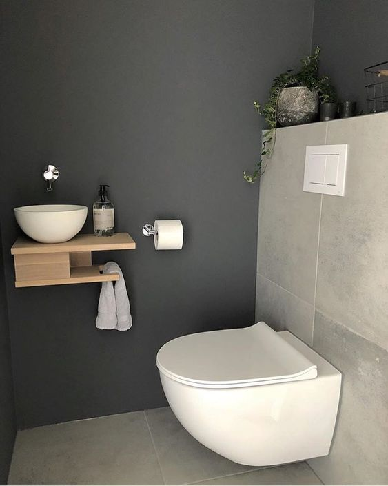 a tiny guest toilet with stone tiles, a wall-mounted wooden vanity with a vessel sink and a potted plant