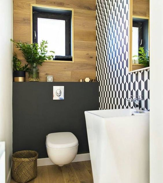 a tony guest toilet with a geometric wall, a free-standing sink, a plywood and matte black wall plus a black framed window