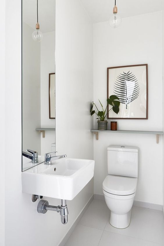 an all-white guest toilet with a wall-mounted sink, a tall mirror, a plant and a tropical artwork