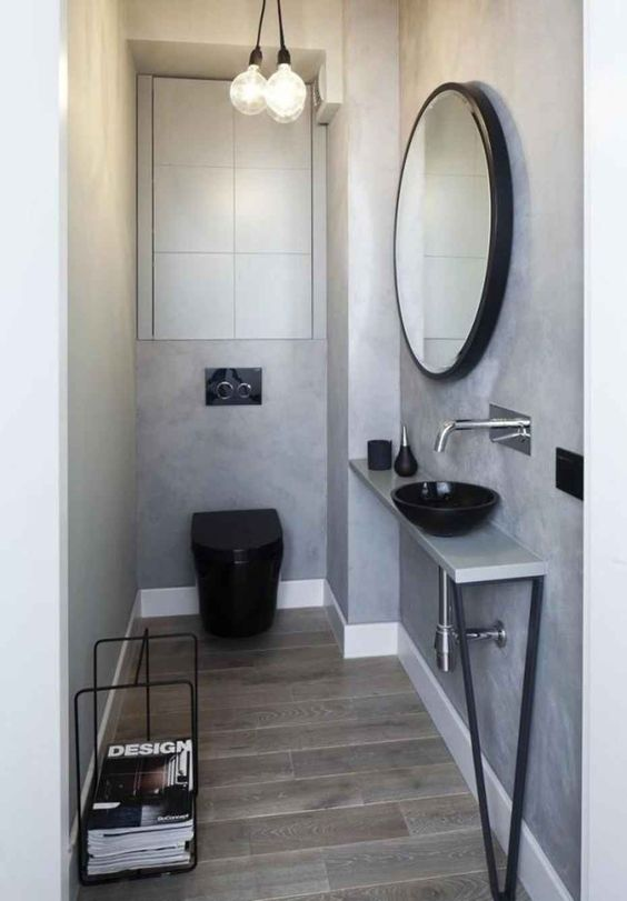 an industrial guest toilet done with concrete, a sleek vanity with a metal leg, a blakc toilet and some bulbs