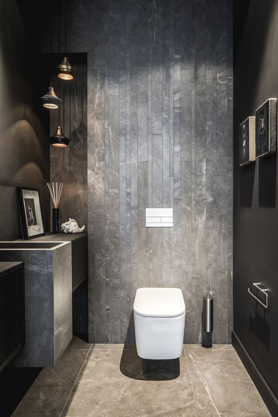 an industrial guest toilet done with concrete and stone, a cluster of pendant lamps, a stone sink and some art