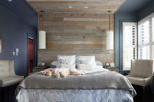 an enjoyable bedroom with a navy and grey part separated with a large weathered wood roof over the bed, grey bedding and creamy furniture