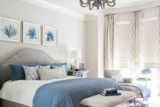 a sea-inspired bedroom with a grey floor, walls, curtains and an upholstered bed plus blue textiles and artworks