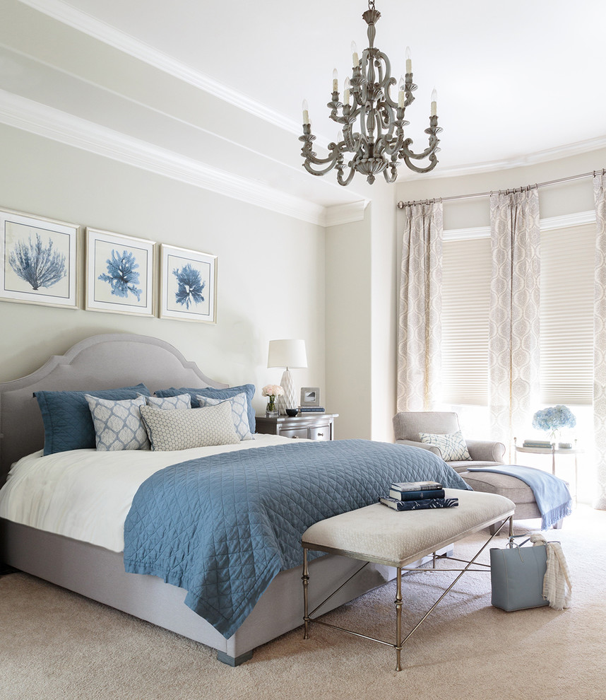 a sea inspired bedroom with a grey floor, walls, curtains and an upholstered bed plus blue textiles and artworks