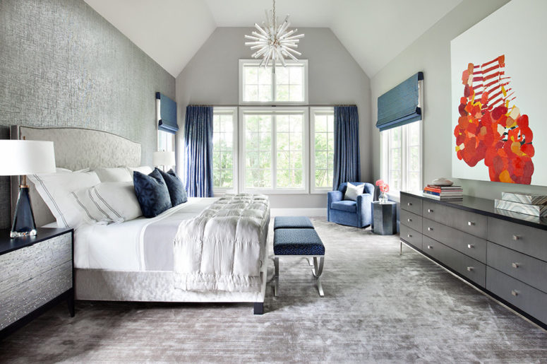a luxurious grey bedroom dotted with navy blue accents - stools, curtains, Roman shades and pillows