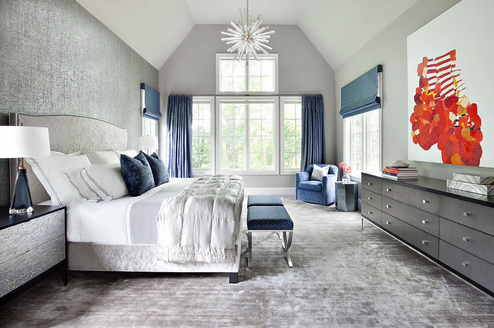 a luxurious grey bedroom dotted with navy blue accents   stools, curtains, Roman shades and pillows
