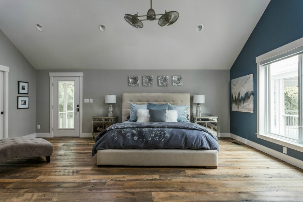 an attic bedroom done in dove grey with a statement blue wall and blue bedding