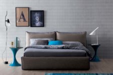 a bold contemporary bedroom with grey wallpaper walls, an upholstered bed, grey and turquoise rugs and turquoise accents here and there