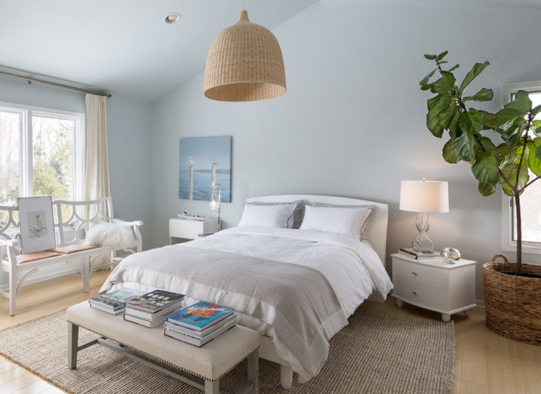a creamy, dove grey and light blue bedroom with a wicker lampshade, some grey textiles and creamy furniture