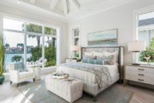 an ocean-inspired bedroom done in dove grey and cremay shades plus bright blue touches and a panoramic window to enjoy the views